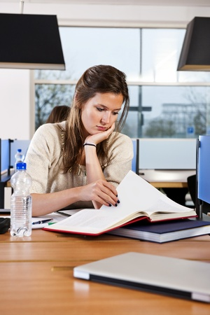 university text: Pretty student, concentrating on a text book, studying in a library Stock Photo