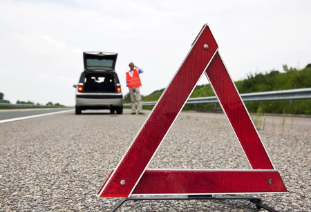 broken car: Road side warning triangle, warning oncoming traffic of a broken down car, with a man using his cell phone to call for assistance Stock Photo