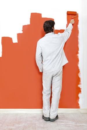 decorando: El hombre, pintar una pared con pintura naranja y un rodillo de pintura