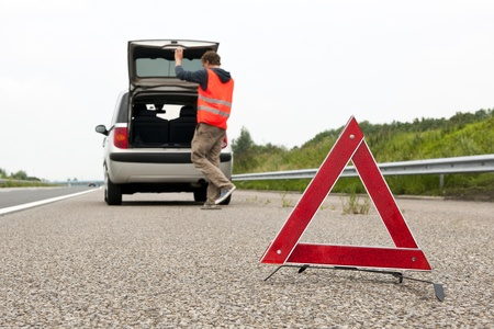 emergency lane: Warning triangle behind a broken down car with the bonnet open on the emergency lane of a highway Stock Photo