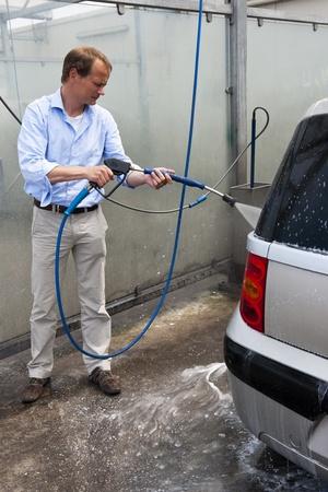autolavaggio: L'uomo, innaffiando la sua auto in un fai da te autolavaggio, utilizzando un getto d'acqua ad alta pressione