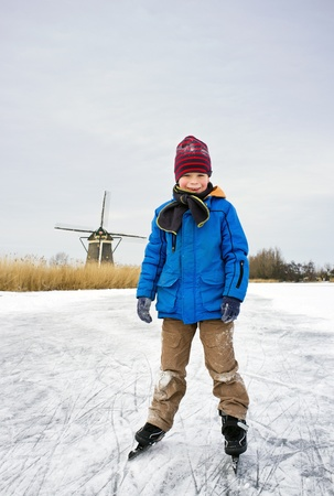 Young child, skating and smiling into the camera on the ice of a frozen canal in typical Dutch scenery photo