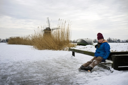 excersise: Young boy, resting on a small jetty during an ice skating trip on a frozen Dutch canal Stock Photo