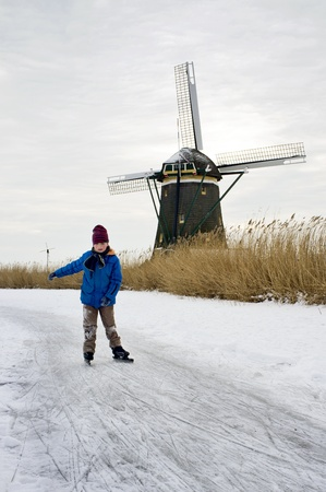 excersise: Young boy, ice skating on a frozen canal in a Dutch rural area, with a windmill in the background Stock Photo