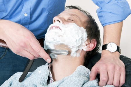 Man, relaxing in a barbers chair, being shaved photo