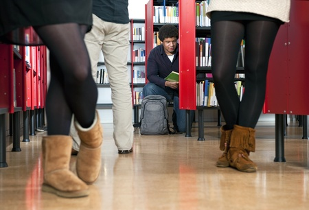 Kneeling man, reading a book in a public library Stock Photo - 12627661