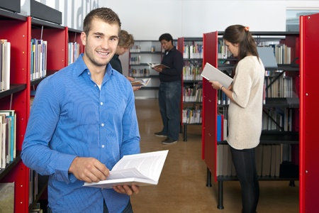 Man, smiling into the camera, whilst browing through a book, surrounded by bookshelves in a public library with several other customers in the background photo
