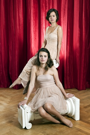 goddesses: Theatrical portrait of two women in evening dresses, sitting on two hellenic ionic columns on a stage in front of a red curtain Stock Photo