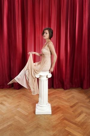 vestido de noche: mujer joven, sentada en un griego - iónicos - pilar en un vestido de noche largo