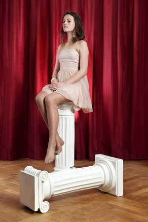 bare feet girl: Young woman, sitting bare foot on an ionic pillar, looking haughty into the camera