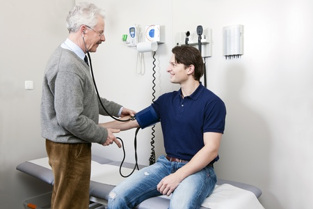 general practitioner: General practitioner taking the blood pressure off a young patient