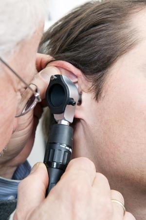 dolor de oido: Practicante general utilizando un ocular para examinar el oído interno de un paciente