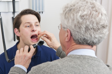 general practitioner: General practitioner examining mouth and throat of a patient with laryngitis