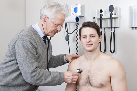 general practitioner: General practitioner using a stethoscope to listen to a young patients chest Stock Photo