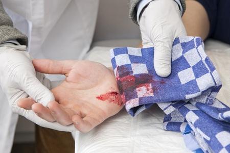 herida: Doctor, el examen de un corte de hemorragia grave en la palma de la mano de un paciente