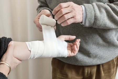 Doctor applying bandage on patients wounded hand at the clinic photo