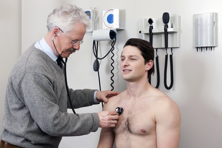 Mature physician examining patient with a stethoscope at clinic photo