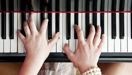 Womans hands striking a chord on the keys of a black lacquered piano photo