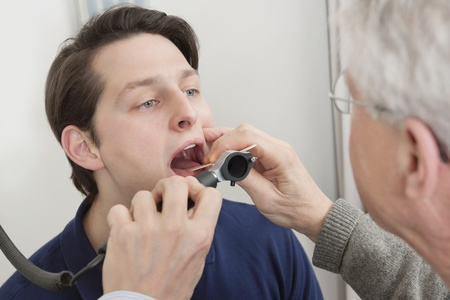 Young man getting his throat checked by male doctor at clinic photo