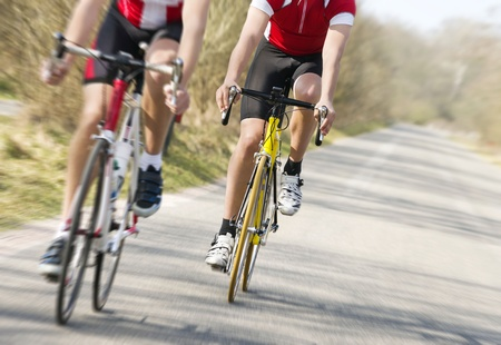 velo: Two cyclists on road racing bicycles in pursuit, focus on the cyclist in the center, motion blurred image Stock Photo