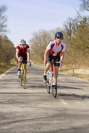 straining: Two Cyclists straining themselves, climbing up a hill on a bicycle