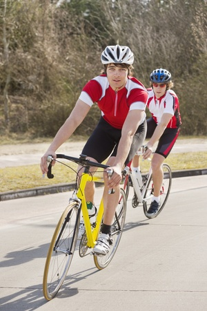 Two cyclists follwing eachother through a curve in the road Stock Photo - 13004175