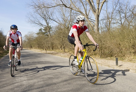 Two cyclists overtaking on a small rural road  Stock Photo - 13004145
