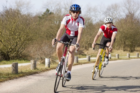 inwards: Two cyclists leaning inwards in the curve of a road during a training tour on a sunny spring day