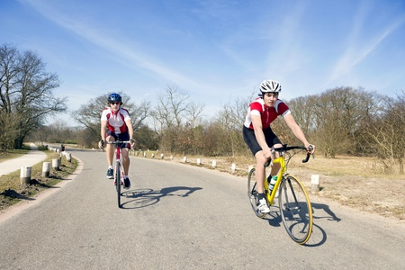 individual sports: Two cyclists on the road touring at speed