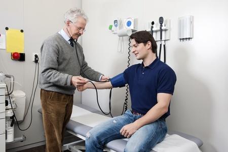 Freundlich Arzt unter einer Blutdruckmessung von einem jungen Patienten während einer körperlichen Untersuchung Standard-Bild