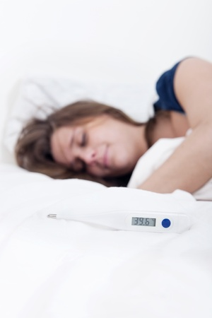 celcius: Thermometer on the duvet indicating 39,6 degrees Celcius, with Sick young woman lying in bed with high fever, out of focus, in the background