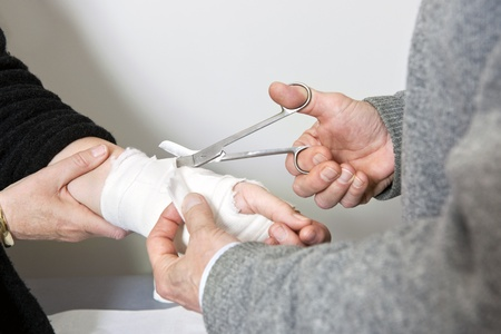 sprained: Doctor cutting through the bandage around an injured womans sprained wrist