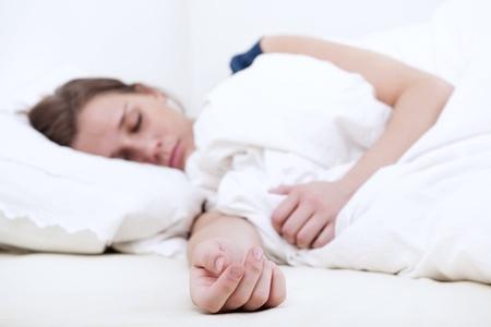 Junge Frau fest schlief im Bett, auf der ausgestreckten Hand konzentrieren sich auf die Matratze