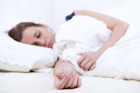 Young woman sleeping soundly in bed, focus on her outstretched hand on the mattress photo