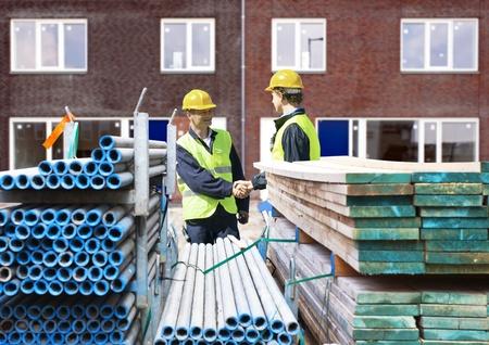 andamio: Dos contratistas de obras agitando las manos detrás de pilas de material de andamiaje, frente a un complejo de edificios residenciales recién terminado Foto de archivo