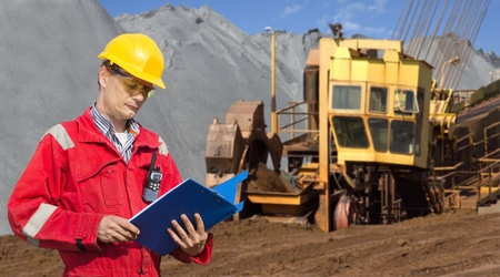 mining equipment: A foreman in a mining site, checking the logs in a blue folder, with a huge wheel digger in the background Stock Photo