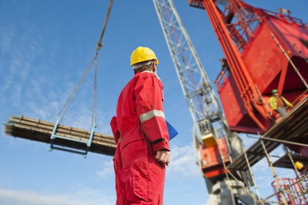 sized: Construction operator looking at a crane carrying scaffolding materials to a super sized structure at a building site