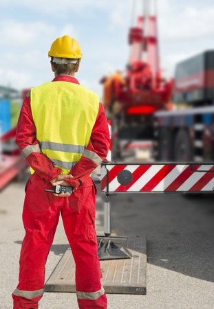 construction safety: Engineer with a radio behind his back supervising the construction works on a rig Stock Photo