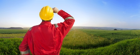 Engineer in overalls and a hard hat in a beautiful countryside, surrounded by nature, imagining big engineering plans photo