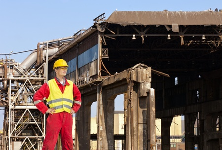 Demolition engineer standing in front of an old factory building, being torn down Stock Photo - 13903776