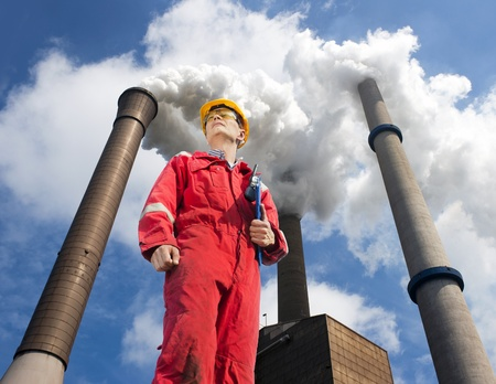 environmental safety: Engineer looking up towards the wind direction with tall smoke stacks, emitting vaporized water, seen from below