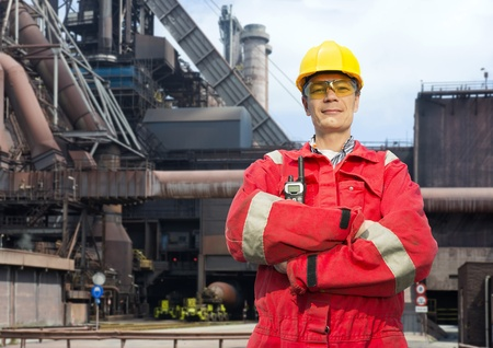 coveralls: Factory worker posing in front of a blast furnace, wearing safety gear, including a hard hat, goggles and fire retardant coveralls