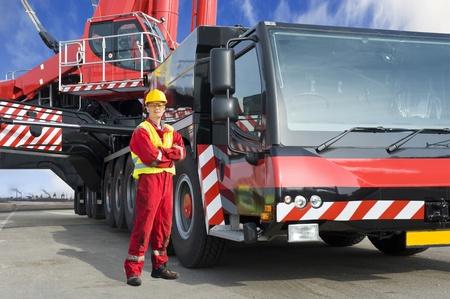 camion grua: Conductor de la grúa, posando junto a la enorme grúa móvil que está operando