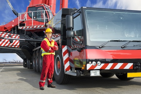 Kranführer, posiert neben dem riesigen mobilen Kran hat er den Betrieb