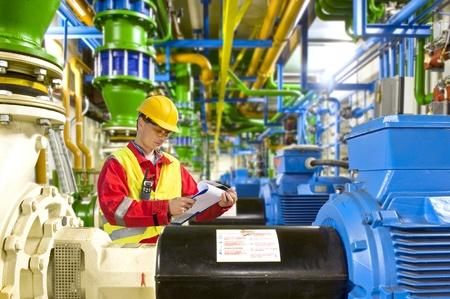 mecanica industrial: Ingeniero busca aty una lista de verificación durante el trabajo de mantenimiento en una sala de máquinas industriales de gran