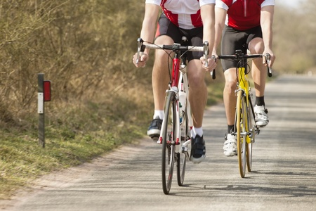 Low section of male athletes riding bicycles on a country road Stock Photo - 13929347