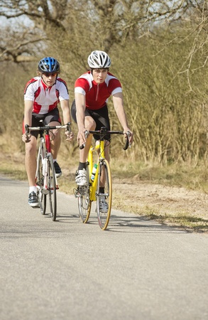 'cycles: Two active male athletes riding cycles in a rural area Stock Photo
