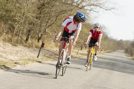 ciclos: Dos j�venes atletas de montar ciclos en una carretera de campo abierto