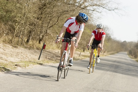 sportsperson: Two young athletes riding cycles on an open country road