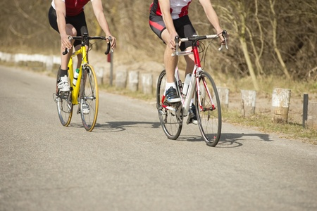 racing bicycle: Low section of male athletes riding bicycles on a country road